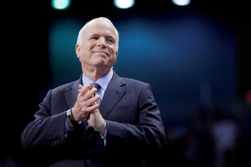 Senator John McCain listens as he is introduced at a campaign rally in Fayetteville, North Carolina.