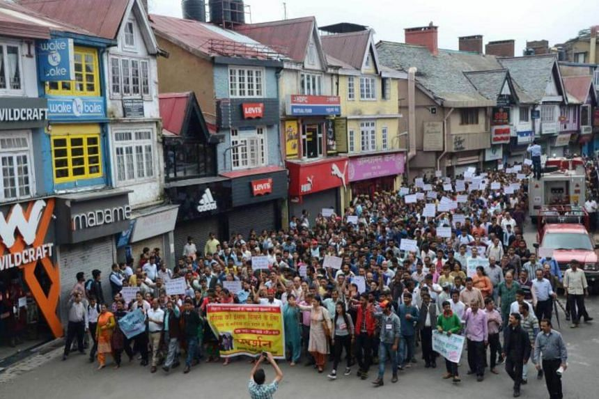 Demonstrators march along a street during a Shimla Nagrik Sabha rally against the rape and murder of a teenage girl in Kotkhai, Shimla district in the northern Indian state of Himachal Pradeshon on July 20, 2017.