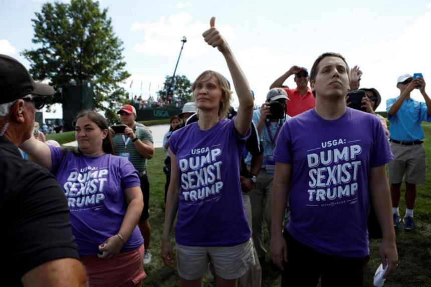 Protesters wearing anti-Trump shirts look up toward US President Donald Trump as he waves to supporters at the US Women's Open golf tournament at Trump National Golf Club in Bedminster, New Jersey, US on July 16, 2017.