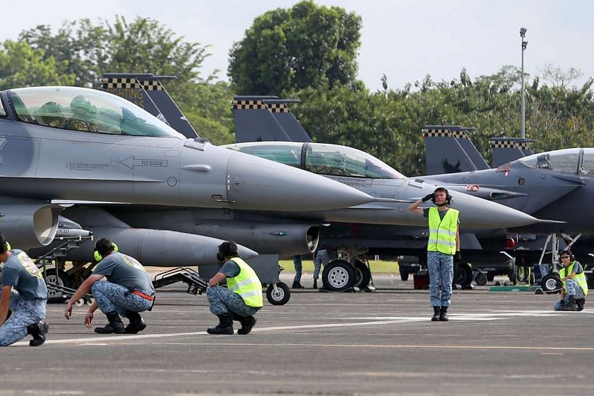A ground marshall saluting the pilot of an F-16 as he prepares to take off from Tengah Air Base on Jan 27, 2016.