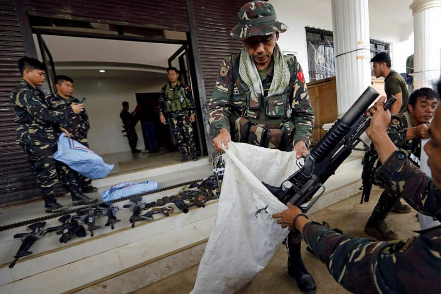 Philippines army soldiers store seized combat weapons in bags after a news conference, as government troops continue their assault against insurgents from the Maute group in Marawi city, Philippines on July 4, 2017.