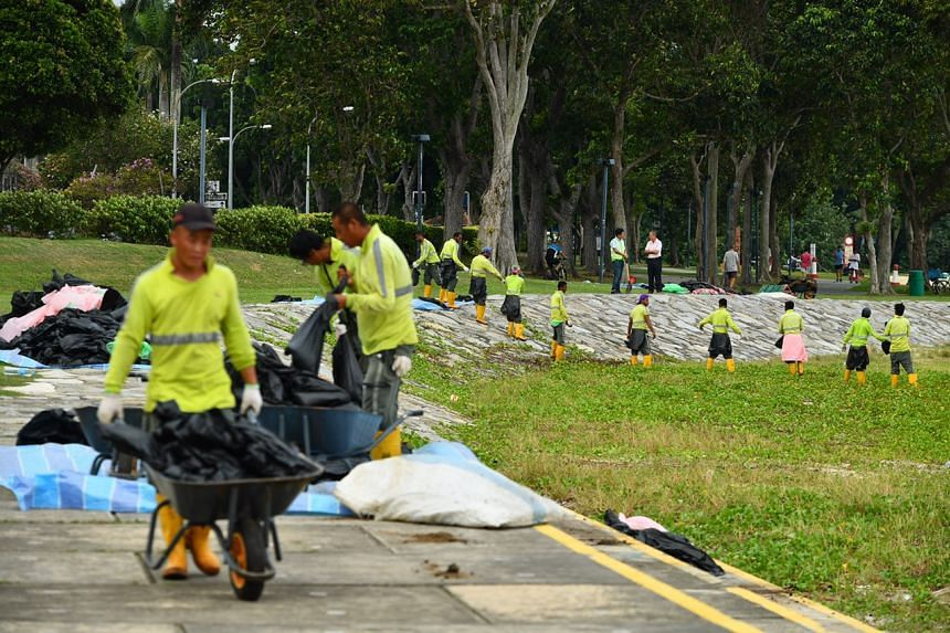 Contractors from NEA removing bags of oil stained sand from the beach affected by the oil spill at East Coast Park as at 5.30pm.