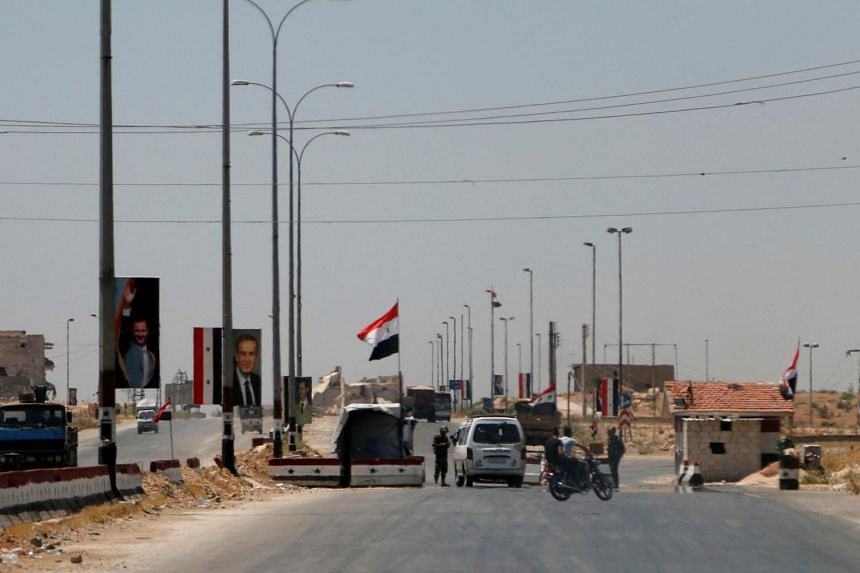 Members of Syrian forces loyal to Syria's President Bashar al-Assad monitor a checkpoint on the main road to Aleppo, Syria.