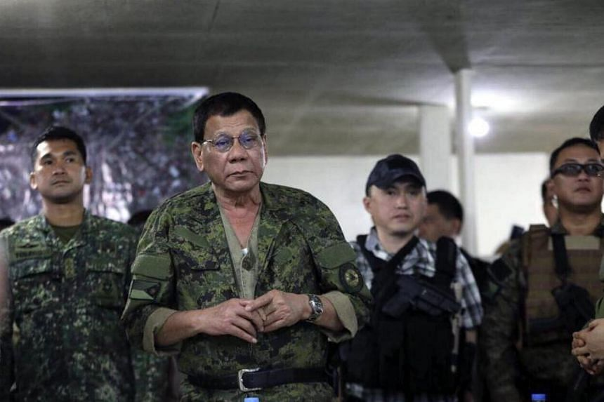 A handout photo made available by Philippine Army shows Philippine President Rodrigo Duterte (second from left) meeting government troops during a visit at a military camp in Marawi city, southern Philippines, 20 July 2017.