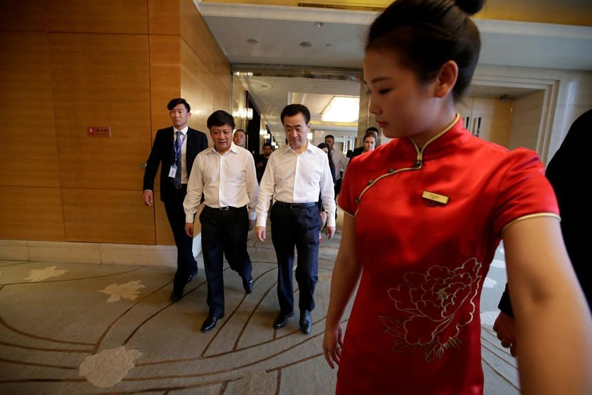 Dalian Wanda Group chairman Wang Jianlin (centre) and Sunac chairman Sun Hongbin arriving for a strategic cooperation signing ceremony in Beijing yesterday. Wanda will now sell a 91 per cent total stake in 13 tourism projects to Sunac China for 43.8