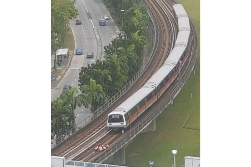 Workers fix a loose clamp on the running rail northbound of Choa Chu Kang station.