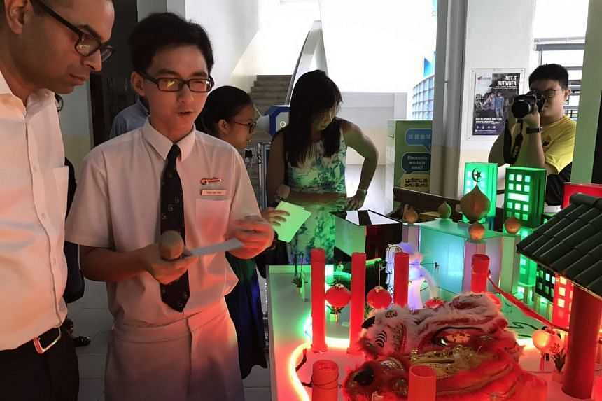 Secondary 2 student Yeoh Lin Feng showing Dr Janil Puthucheary the interactive display on cultural diversity in Singapore on July 21, 2017.