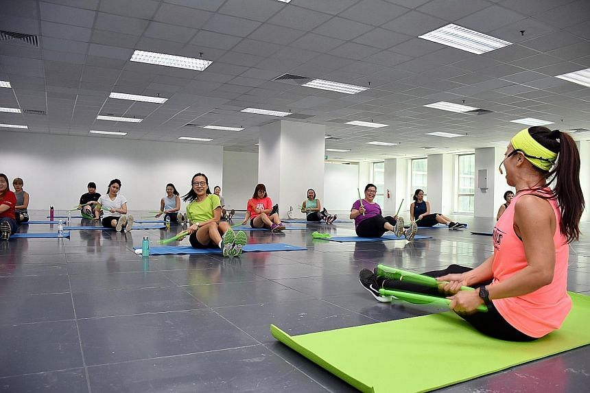 A lunchtime workout at the OUE Downtown building. The Tripartite Oversight Committee on Workplace Health's programmes include health checkups for older workers in hard-to-reach industries, workplace workouts and putting healthier dishes on canteen me