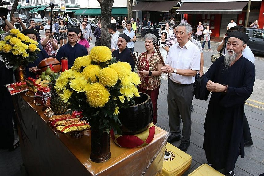 Left: Prime Minister Lee Hsien Loong and Mrs Lee with (from far left) inter-faith activist Hassan Ahmad and IRO members Imam Hassan Al-Attas of Ba'alwie Mosque, Lutheran Bishop Terry Kee and Mr Noor Marican, in front of a trick-eye mural. Above: PM L