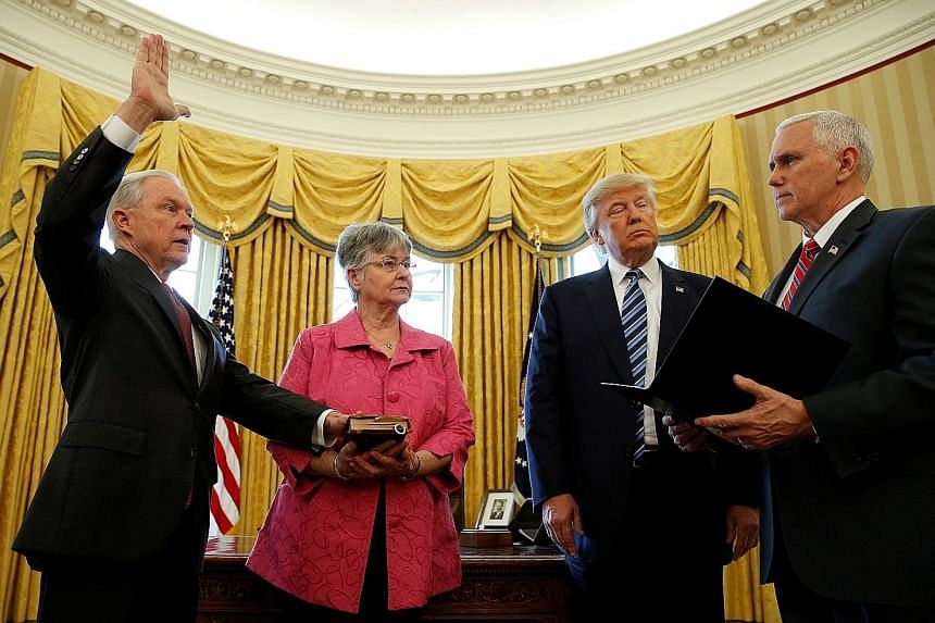 US President Donald Trump observing as Vice-President Mike Pence swears in Attorney-General Jeff Sessions while his wife Mary holds the Bible at the White House on Feb 9.