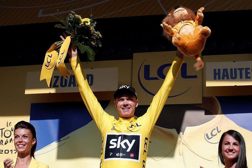 Team Sky rider Chris Froome of Britain celebrates on the podium, wearing the overall leader's yellow jersey.