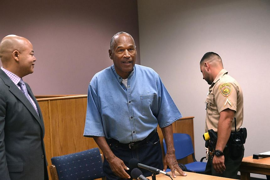 O.J. Simpson gets up as his lawyer Malcolm LaVergne (left) looks on during his parole hearing at Lovelock Correctional Center in Nevada, on July 20, 2017.