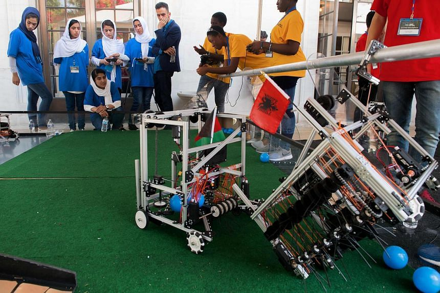 Members of the Afghani all-girls robotics team watch as their robot bumps a robot from Albania (right) in the practice area at the DAR Constitution Hall, in Washington, DC on July 17, 2017.