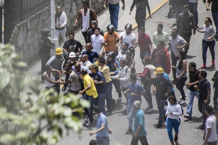 A protester is detained by workers near the offices of state-owned Venezolana de Television (VTV) television station in Caracas, Venezuela on July 20, 2017.