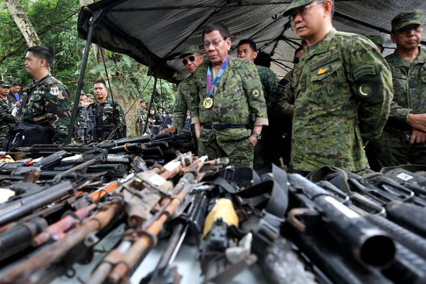 Philippine President Rodrigo Duterte inspects firearms together with Eduardo Ano, Chief of Staff of the Armed Forces of the Philippines, during his visit at the military camp in Marawi city, southern Philippines on July 20, 2017.