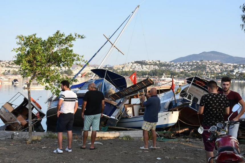 People watch damaged boats at a beach following a sea surge caused by an earthquake, in the Agean coastal city of Mugla, Bodrum Province, Turkey, on July 21, 2017.