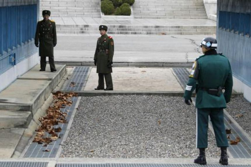 North Korean soldiers look across a concrete border as a South Korean soldier (right) stands guard at the truce village of Panmunjom.