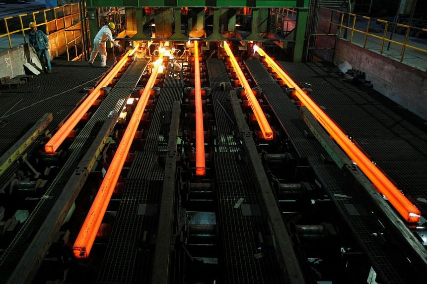 Employees work in a Hangzhou Iron and Steel Group Company workshop in Hangzhou, Zhejiang province, on Aug 4, 2009.