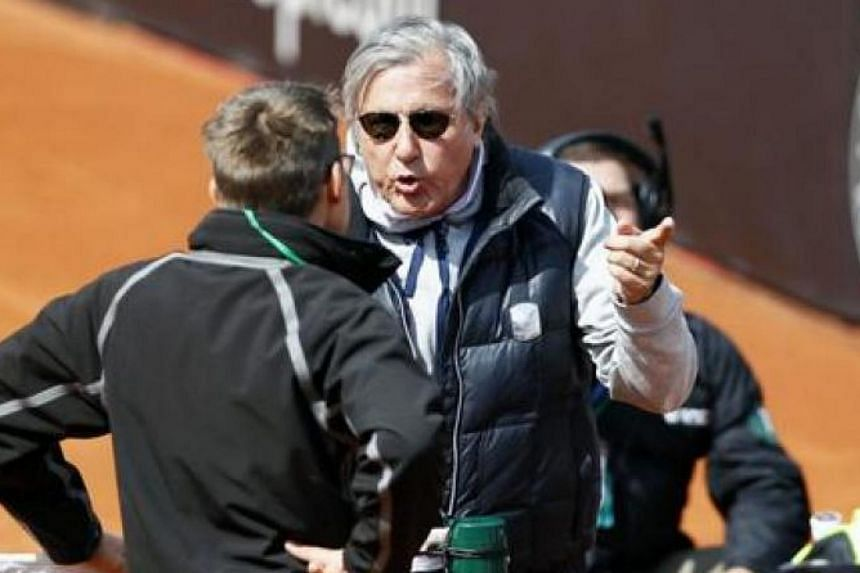 Romania's Fed Cup team captain Ilie Nastase (centre) argues with an ITF official during the Fed Cup World Group II playoff tie between Romania and Britain in Constanta, Romania, on April 22, 2017.