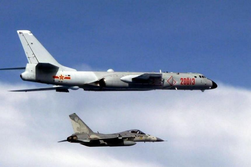 A handout photo made available by Taiwan's Defense Ministry shows an AIDC F-CK-1 Ching-kuo Taiwan Air Force Indigenous Defense Fighter (IDF) jet (bottom) intercepting a Chinese H-6 bomber (top) after the bomber entered Taiwan's Air Defense Identifica