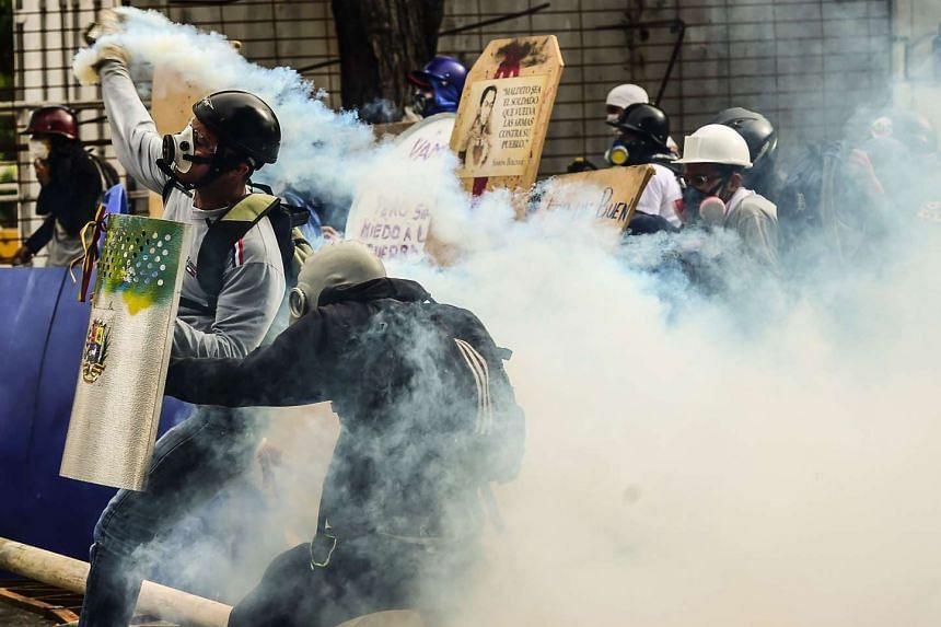 Opposition demonstrators clash with riot police during an anti-government protest in Caracas, on July 20, 2017.