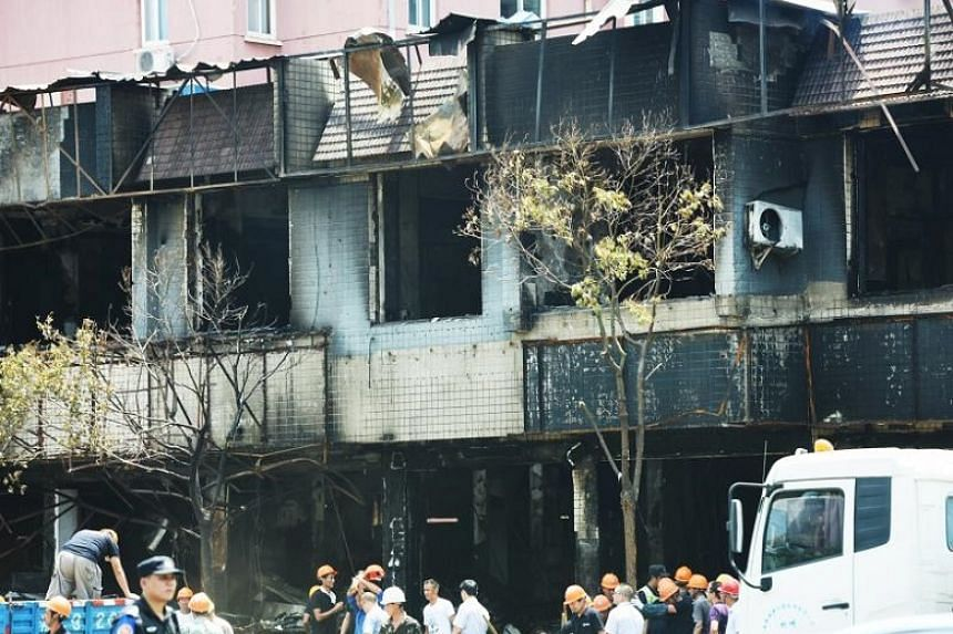 Workers arrive at shops which burnt after an explosion in a restaurant in Hangzhou, China, on July 21, 2017.