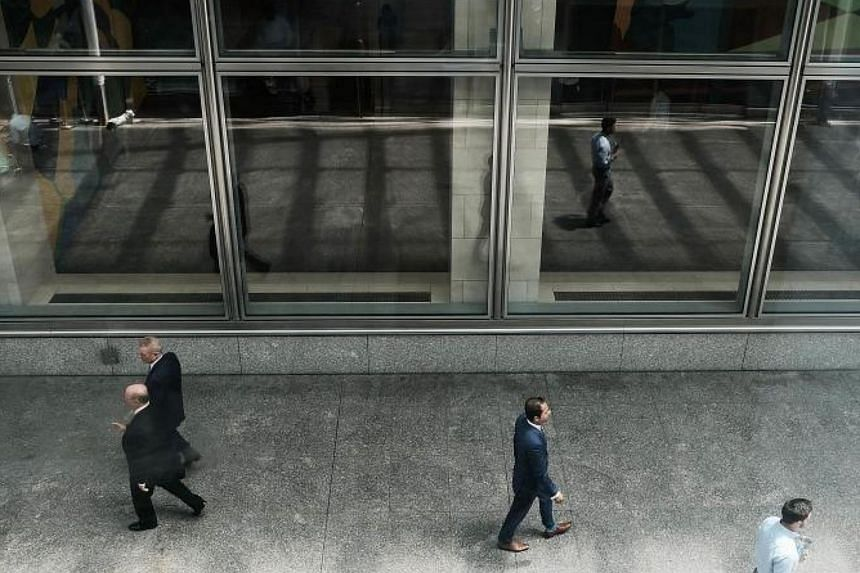 People walk by the Goldman Sach's New York headquarters in New York City on July 18, 2017.