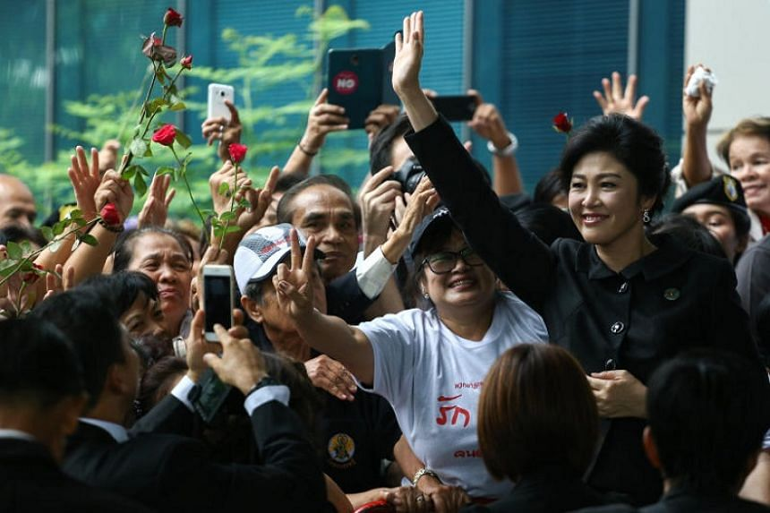 Ousted former Thai prime minister Yingluck Shinawatra greets supporters as she arrives at the Supreme Court in Bangkok, Thailand, on July 21, 2017.