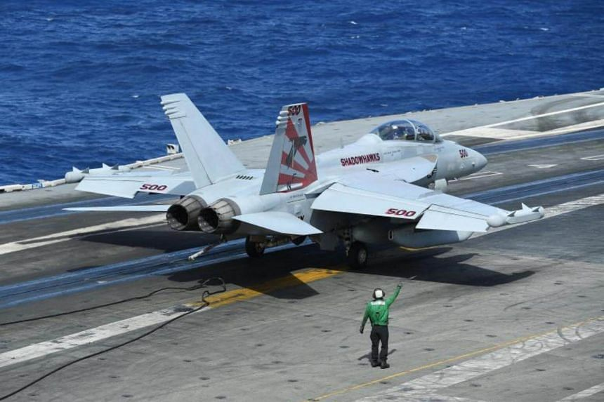 An F/A-18F Super Hornet releases the arresting cable after landing on-board the USS Ronald Reagan in the Coral Sea, on July 20, 2017.
