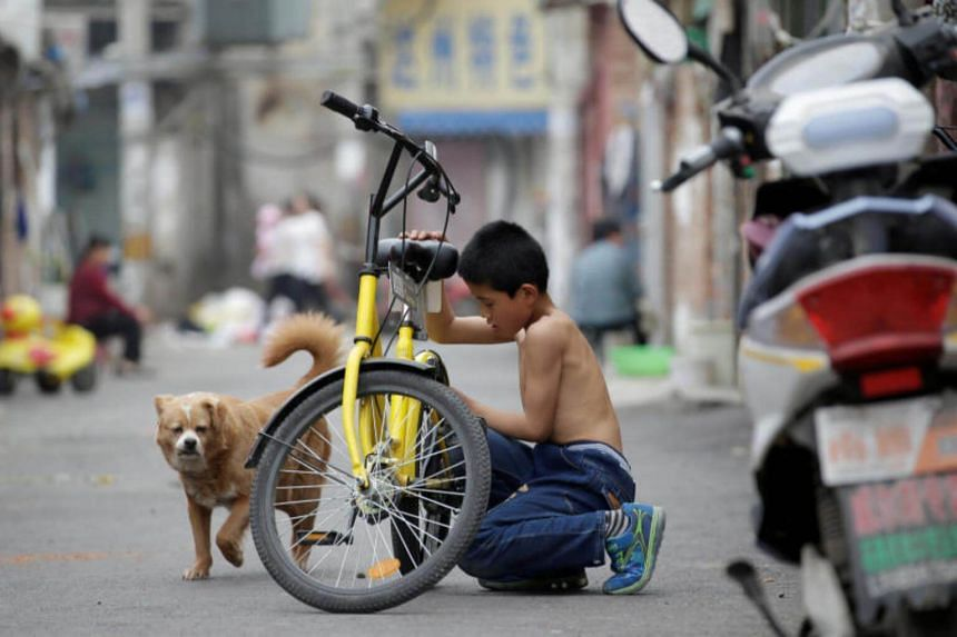 A boy checks a destroyed Ofo's shared bike at a residential area for migrant workers in a village on the outskirts of Beijing.