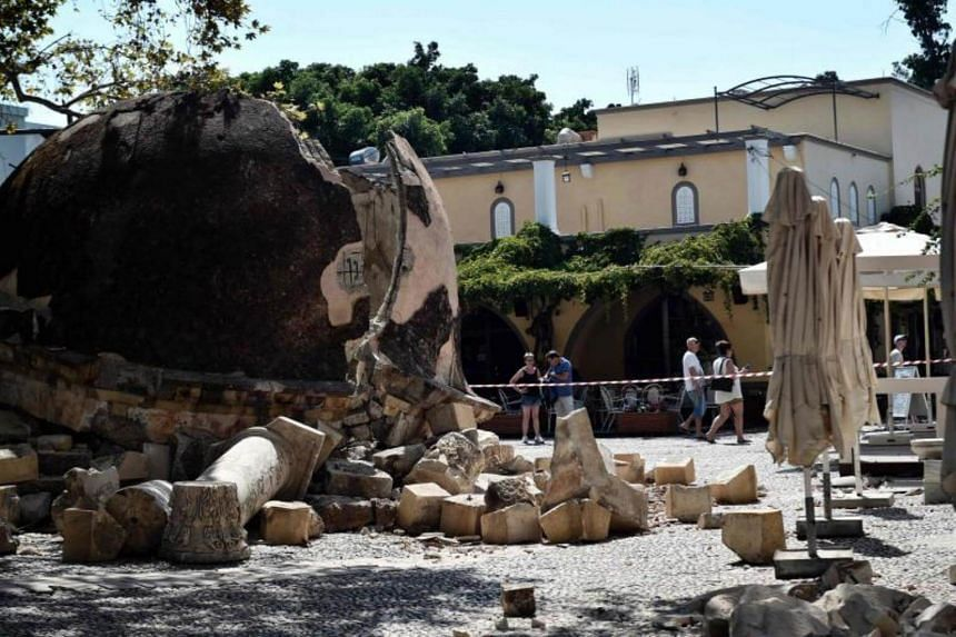 Tourists look at damages on the Kos island on July 22, 2017, following a 6.5 magnitude earthquake which struck the region.