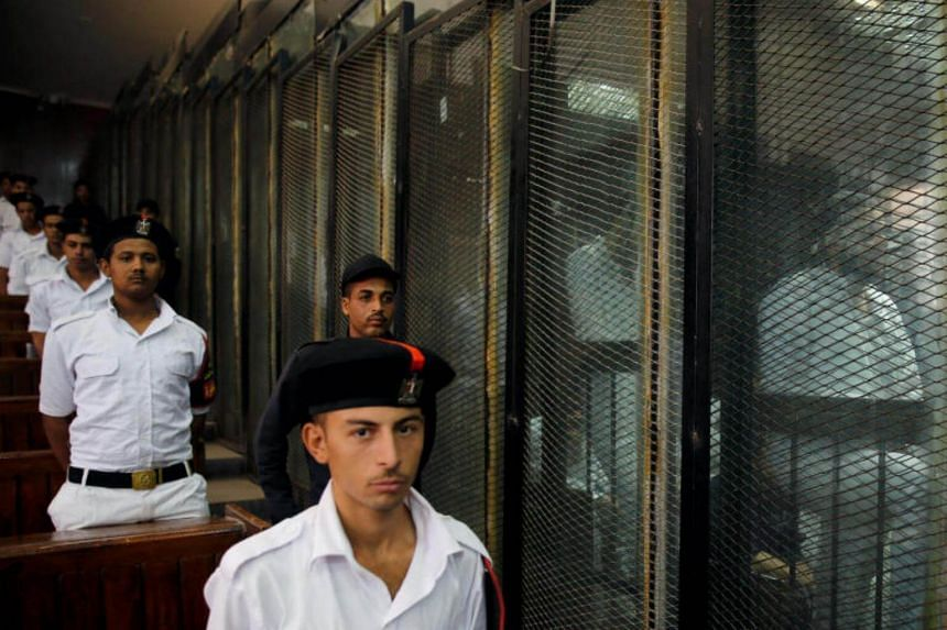 Police officers stand guard as defendants accused of involvement in the 2015 assassination of Egypt's top prosecutor are seen in a cage in a courtroom, on the outskirts of Cairo, on June 17, 2017.