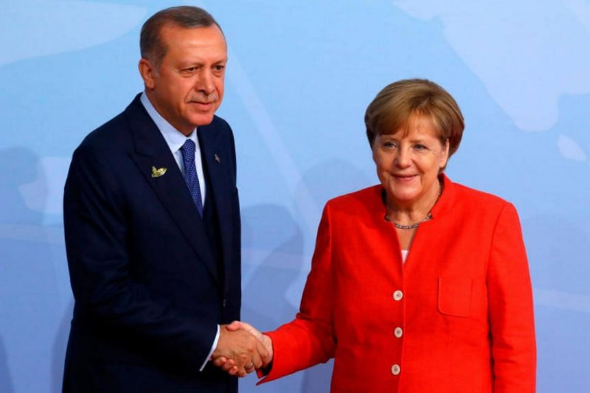 Turkish President Recep Tayyip Erdogan shakes hands with German Chancellor Angela Merkel as he arrives for the G20 leaders summit in Hamburg, Germany, on July 7, 2017.
