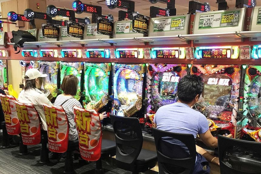 Top: A long queue forms outside a pachinko parlour near a train station in Tokyo before its doors even open one morning in May. Above: Pachinko machines are easy to play, readily available and cheap, drawing in an array of Japanese people from commut