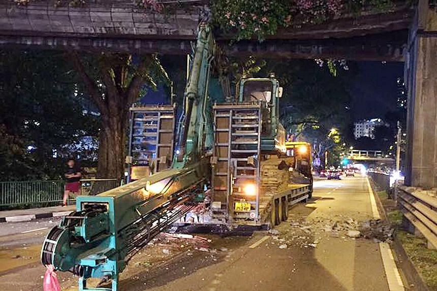 The arm of the excavator - which was being ferried by a trailer - lodged in the overhead pedestrian bridge in Balestier Road, part of which was closed after the accident last night.