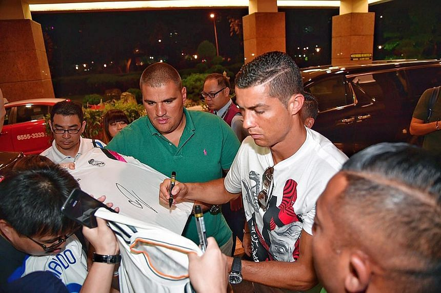 Ronaldo signing autographs for fans outside Great World City in the evening.