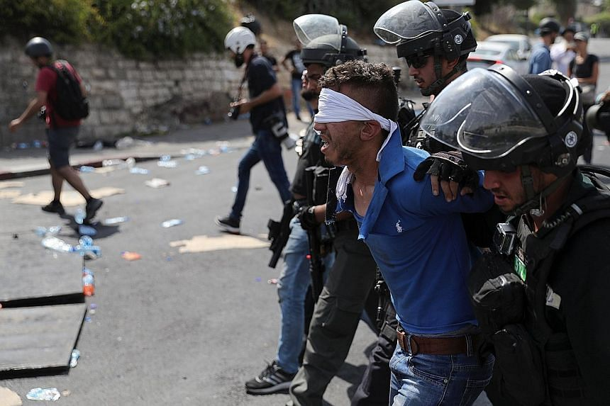 Israeli security forces arresting a Palestinian man following clashes outside Jerusalem's Old City yesterday, which broke out over the non-removal of metal detectors at the entrances to the Haram al-Sharif mosque compound.