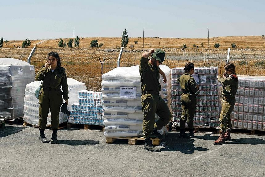Israeli soldiers with food supplies for Syrian refugees at an army base in the Golan Heights on Wednesday. The aid project represents what Israeli officials say is a longer- term investment in stabilising the border area.