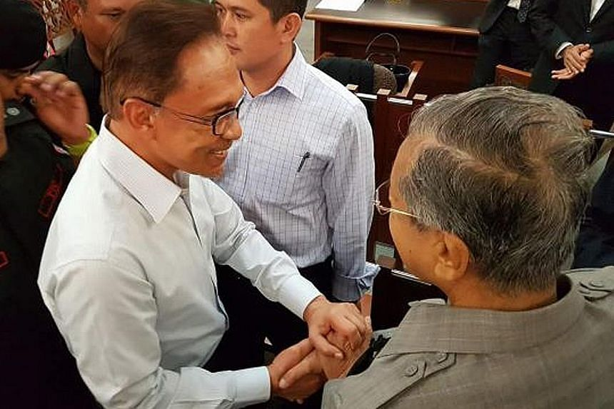 "Dr Mahathir Mohamad (right) greeting Anwar Ibrahim in the Kuala Lumpur High Court on Sept 5 last year. The former Malaysian premier said both he and Anwar are ""not angry over the past""."