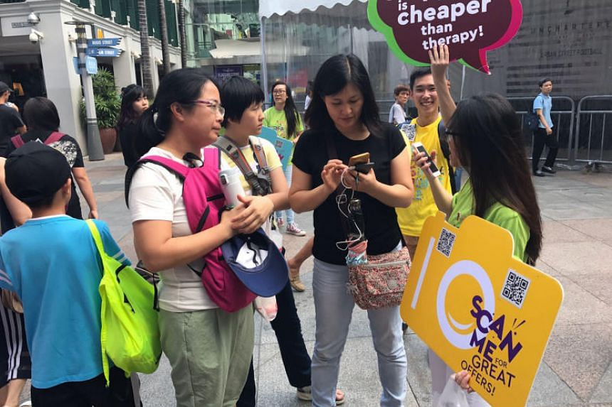 GoSpree rovers showing shoppers the way to use the GoSpree app outside Bugis Junction on July 22, 2017.