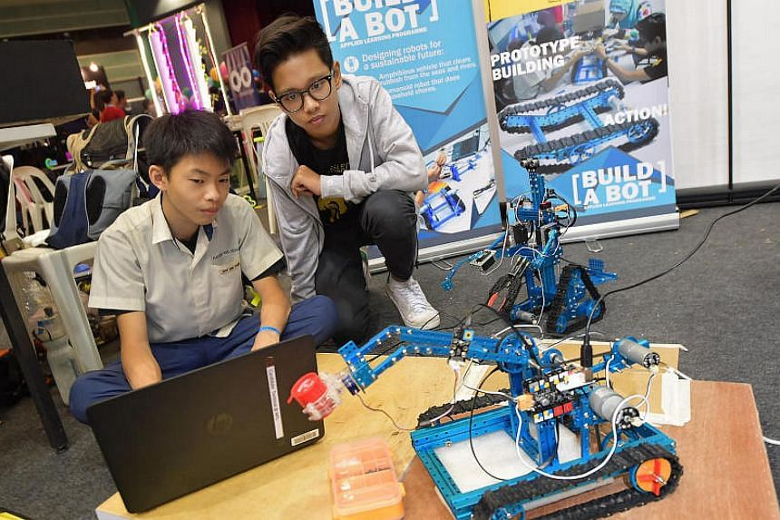 Fuchun Secondary School's Sew Zee Cheen (left) and Muhammad Rafyuddean Michael, with an amphibious vehicle that clears rubbish from the seas and waters (front) and a humanoid robot that does household chores.