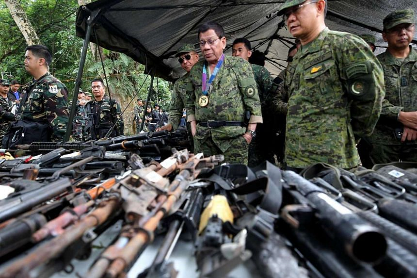 Philippine President Rodrigo Duterte inspects firearms together with Eduardo Ano, Chief of Staff of the Armed Forces of the Philippines in Marawi city, southern Philippines on July 20, 2017.