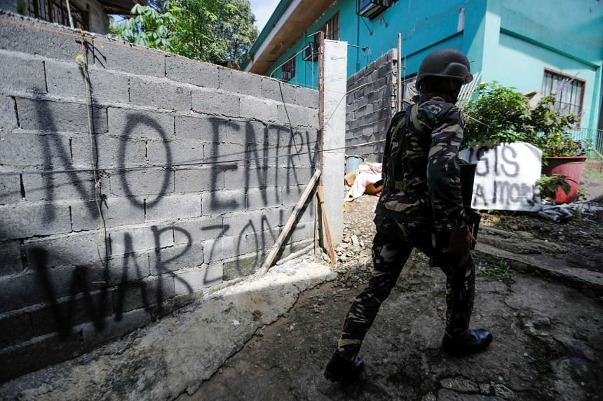 A Filipino soldier walks as government troops continue their assault against insurgents from the Maute group in Marawi city, Philippines on July 1, 2017.