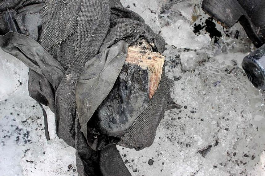 This handout picture released on July 19, 2017 by the Swiss Police of Canton Valais shows a book near the remains of a couple found preserved in a receding glacier, near Les Diablerets.