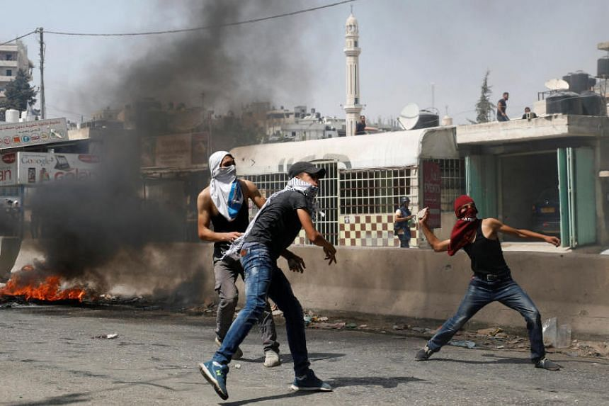 Palestinian protesters hurl stones at Israeli troops during clashes near the West Bank city of Ramallah on July 21, 2017.