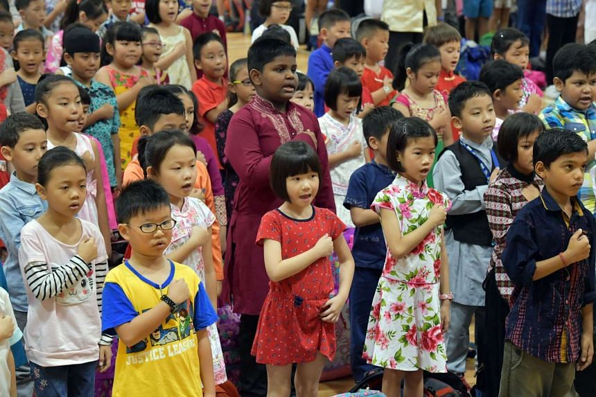 Guangyang Primary pupils reciting the pledge yesterday, with some dressed in traditional costumes as part of Racial Harmony Day celebrations.