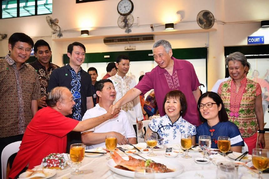 Prime Minister Lee Hsien Loong shaking hands with Mr Koh Ting Beow, a Pioneer Generation Ambassador.