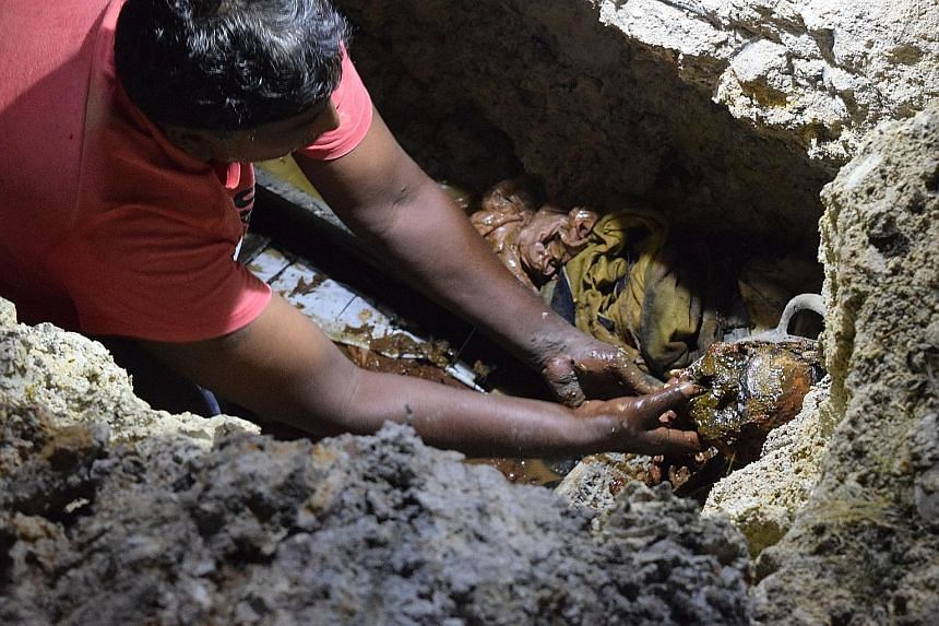Far left: The gravedigger has to sift through mud, soil and other debris with his bare hands to recover the remains. Left: Yin Fengshui practitioner Fong Chun Cheong with the cremated remains.