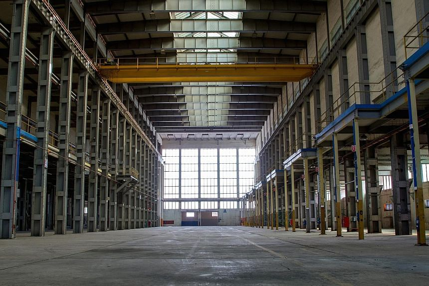 """Above: Visitors can sign up for guided tours of places like the """"A"""" power station in Pasir Panjang, which was built in the 1950s. Left: The now empty turbine hall."""