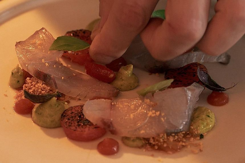 Watch a video which shows barramundi being prepared at a restaurant kitchen (left: cured barramundi, watermelon with tomato vinaigrette and avocado from Pollen).